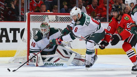 May 3, 2015; Chicago, IL, USA; Chicago Blackhawks left wing Brandon Saad (20) and Minnesota Wild defenseman Marco Scandella (6) chase the puck in front of goalie Devan Dubnyk (40) during the first period in game two of the second round of the 2015 Stanley Cup Playoffs at the United Center. Mandatory Credit: Dennis Wierzbicki-USA TODAY Sports