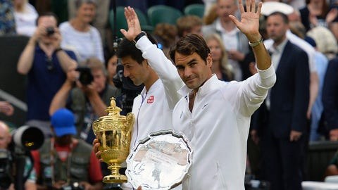 Serbia's Novak Djokovic (L) and Switzerland's Roger Federer carry their trophies as they leave the court following their men's singles final match presentation on day thirteen of the 2015 Wimbledon Championships at The All England Tennis Club in Wimbledon, southwest London, on July 12, 2015. Djokovic won the match 7-6, 6-7, 6-4, 6-3. RESTRICTED TO EDITORIAL USE  --  AFP PHOTO / GLYN KIRK        (Photo credit should read GLYN KIRK/AFP/Getty Images)