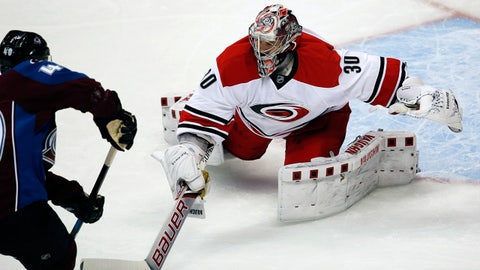 Carolina Hurricanes goalie Cam Ward, right, reaches out to deflect shot off the stick of Colorado Avalanche left wing Alex Tanguay during the first period of an NHL hockey game Wednesday, Oct. 21, 2015, in Denver. (AP Photo/David Zalubowski)