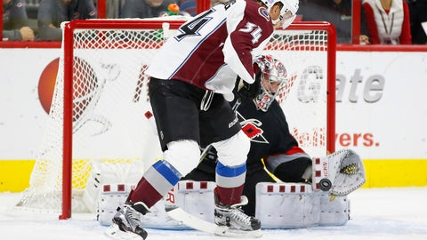 Oct 30, 2015; Raleigh, NC, USA;  Carolina Hurricanes goalie Cam Ward (30) makes a save in front of Colorado Avalanche forward Carl Soderberg (34) during the first period at PNC Arena. Mandatory Credit: James Guillory-USA TODAY Sports