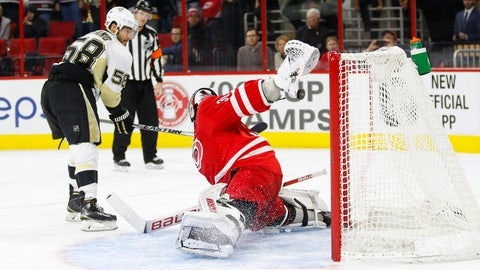 Feb 12, 2016; Raleigh, NC, USA;  Pittsburgh Penguins defensemen Kris Letang (58) watches his shoot out game winning goal against Carolina Hurricanes goalie Cam Ward (30) at PNC Arena. The Pittsburgh Penguins defeated the Carolina Hurricanes 2-1 in the shoot out. Mandatory Credit: James Guillory-USA TODAY Sports