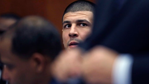 Former New England Patriots NFL football player Aaron Hernandez, center, sits with his defense team during a court appearance at Suffolk Superior Court in Boston, Wednesday, Dec. 7, 2016. Hernandez, who is serving a life sentence for the 2013 killing of Odin Lloyd, appeared with his lawyers in a status conference before for his upcoming trial, where he is charged in the 2012 slayings of two men outside a Boston nightclub. (AP Photo/Charles Krupa)