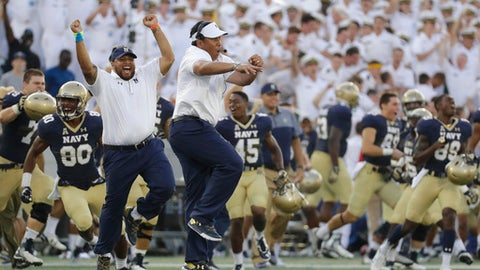FILE - In this Sept. 10, 2016, file photo, Navy head coach Ken Niumatalolo, center, celebrates after an NCAA college football game against Connecticut in Annapolis, Md. It doesn't matter that neither Army nor Navy are in the Top 25, or that the Midshipmen have defeated the Black Knights 14 times in a row. The Army-Navy game is Saturday, Dec. 10, 2016, in Baltimore. When their football careers end, each player is obligated to begin serving in the military. Those already in battle will be represented Saturday by several men who may ultimately be by their side. (AP Photo/Patrick Semansky, File)