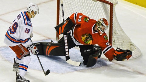 Chicago Blackhawks goalie Scott Darling (33) makes a save against New York Rangers right wing Jesper Fast (19) during the first period of an NHL hockey game on Friday Dec. 9, 2016, in Chicago. (AP Photo/Matt Marton)