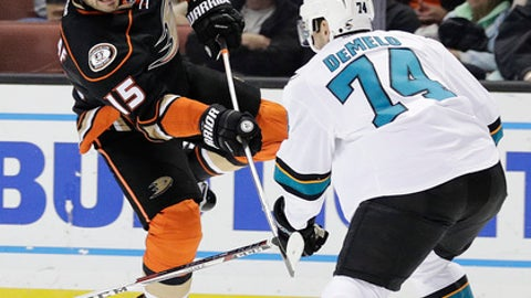 Anaheim Ducks' Ryan Getzlaf, left, shoots as he is defended by San Jose Sharks' Dylan DeMelo during the second period of an NHL hockey game Friday, Dec. 9, 2016, in Anaheim, Calif. (AP Photo/Jae C. Hong)