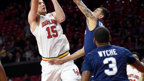 Maryland forward Michal Cekovsky (15) takes a shot against St. Peter's guard Nnamdi Enechionyia, top, and Trevis Wyche (3) during the first half of an NCAA college basketball game, Saturday, Dec. 10, 2016, in College Park, Md. (AP Photo/Nick Wass)