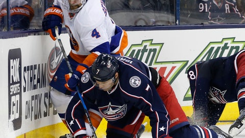 New York Islanders' Dennis Seidenberg, left, of Germany, and Columbus Blue Jackets' Jack Johnson fight for a loose puck during the third period of an NHL hockey game, Saturday, Dec. 10, 2016, in Columbus, Ohio. The Blue Jackets beat the Islanders 6-2. (AP Photo/Jay LaPrete)