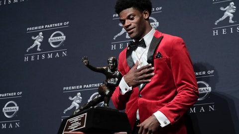 Louisville's Lamar Jackson prepares to pick up the the Heisman Trophy after winning the Heisman Trophy award, Saturday, Dec. 10, 2016, in New York. (AP Photo/Julie Jacobson)