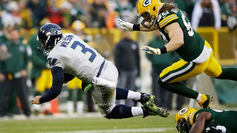 Seattle Seahawks' Russell Wilson runs for a first down during the first half of an NFL football game against the Green Bay Packers Sunday, Dec. 11, 2016, in Green Bay, Wis. (AP Photo/Jeffrey Phelps)