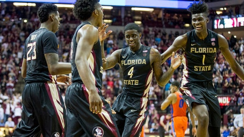 Florida State's Marquez Smith (23), Terrance Mann (14) Dwayne Bacon, Jr. (4) and Jonathan Isaac (1) celebrate a basket in the second half of an NCAA college basketball game against Florida in Tallahassee, Fla., Sunday, Dec. 11, 2016. Florida State defeated Florida 83-78. (AP Photo/Mark Wallheiser)