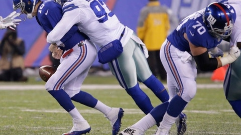 New York Giants quarterback Eli Manning, left, is sacked by Dallas Cowboys' Benson Mayowa, right, as he fumbles the ball during the first half of an NFL football game Sunday, Dec. 11, 2016, in East Rutherford, N.J. The Cowboys recover the ball on the play. (AP Photo/Seth Wenig)
