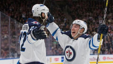 Winnipeg Jets' Marko Dano (56) and Chris Thorburn (22) celebrate a goal against the Edmonton Oilers during the second period of an NHL hockey game in Edmonton, Alberta, Sunday, Dec. 11, 2016. (Amber Bracken/The Canadian Press via AP)
