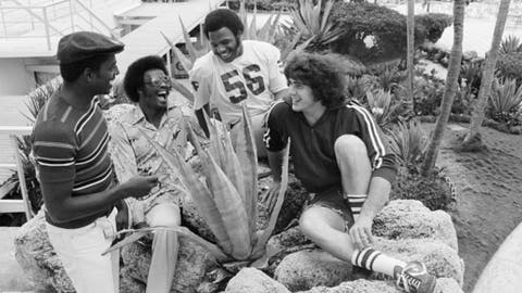 "FILE - In this Dec. 29, 1975, file photo, members of the Oklahoma Sooners college football team relax in the garden of their hotel in Miami Beach, Fla. From left are Victor Brown, Mike Phillips, Glenn Comeaux and James ""Jimbo"" Elrod. The Oklahoma Highway Patrol says former Oklahoma All-American James ""Jimbo"" Elrod, who played on the Sooners' 1974 and 1975 national championship teams, has died in a car wreck. He was 62. The highway patrol says the single-vehicle crash happened at about 3:45 a.m. Monday, Dec. 12, 2016, on Interstate 44 near Chandler, about 60 miles southwest of Tulsa. (AP Photo/Bill Hudson, File)"