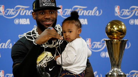 FILE - In this June 19, 2016, file photo, Cleveland Cavaliers' LeBron James answers questions as he holds his daughter Zhuri during a post-game press conference after winning the NBA title by defeating the Golden State Warriors in the NBA Finals. HBO announced on Dec. 12, 2016 that James is producing a documentary on Muhammad Ali for the network. (AP Photo/Eric Risberg, File)