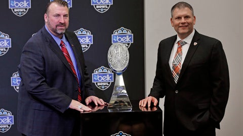 Arkansas head coach Bret Bielema, left, and Virginia Tech head coach Justin Fuente, pose with the trophy during a news conference for the Belk Bowl NCAA college football game in Charlotte, N.C., Tuesday, Dec. 13, 2016. The game will be played on Dec. 29, 2016. (AP Photo/Chuck Burton)