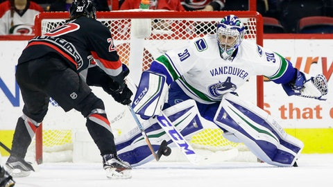 Carolina Hurricanes' Sebastian Aho (20), of Finland, shoots and scores against Vancouver Canucks goalie Ryan Miller (30) during the first period of an NHL hockey game in Raleigh, N.C., Tuesday, Dec. 13, 2016. (AP Photo/Gerry Broome)