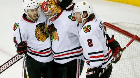 Chicago Blackhawks defenseman Niklas Hjalmarsson (4) and defenseman Duncan Keith (2) congratulate goalie Scott Darling after the Blackhawks beat the New York Rangers 2-1 in an NHL hockey game Tuesday, Dec. 13, 2016, in New York. (AP Photo/Julie Jacobson)
