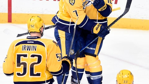 Nashville Predators center Mike Fisher (12) celebrates Yannick Weber (7), of Switzerland, and Matt Irwin (52) after Fisher scored the go-ahead goal against the St. Louis Blues during the third period of an NHL hockey game Tuesday, Dec. 13, 2016, in Nashville, Tenn. The Predators won 6-3. (AP Photo/Mark Zaleski)