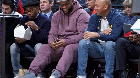 Former New York Yankees shortstop Derek Jeter, right, and New York Yankees pitcher CC Sabathia sit courtside during the first half of an NBA basketball game between the Portland Trail Blazers and the Oklahoma City Thunder in Portland, Ore., Tuesday, Dec. 13, 2016. (AP Photo/Craig Mitchelldyer)