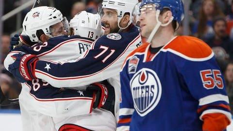 Columbus Blue Jackets' Sam Gagner (89), Cam Atkinson (13) and Nick Foligno (71) celebrate goal as Edmonton Oilers' Mark Letestu (55) skates past during third period NHL hockey action in Edmonton, Alberta, Tuesday Dec. 13, 2016. (Jason Franson/The Canadian Press via AP)