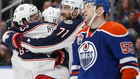 Columbus Blue Jackets' Sam Gagner (89), Cam Atkinson (13) and Nick Foligno (71) celebrate goal as Edmonton Oilers' Mark Letestu (55) skates past during third period NHL hockey action in Edmonton, Alberta, Tuesday Dec. 13, 2016. (Jason Franson/The Canadian Press via AP)