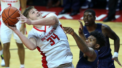Rutgers center C.J. Gettys takes a shot past Fairleigh Dickinson forward Mike Holloway and guard Darian Anderson during the second half of an NCAA college basketball game, Wednesday, Dec. 14, 2016, in Piscataway, N.J. (AP Photo/Mel Evans)