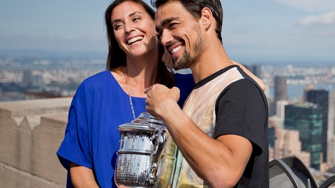 FILe - In this Sept. 13, 2015, file photo, Flavia Pennetta, of Italy, left, poses with her then-fiance and fellow tennis player Fabio Fognini with the U.S. Open tennis women's singles championship trophy during a visit to the Top of the Rock Observation Deck at Rockefeller Center in New York. Flavia Pennetta is expecting her first child. Pennetta, who announced her 2015 retirement from tennis during the trophy presentation after her lone Grand Slam title, and her husband, touring pro Fabio Fognini, issued matching statements on Twitter on Thursday, Dec. 15, 2016, about the pregnancy. (AP Photo/David Goldman)