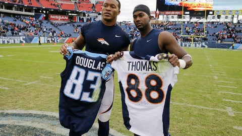 FILE - In this Dec. 11, 2016, file photo, Denver Broncos wide receiver Demaryius Thomas, left, and Tennessee Titans wide receiver Harry Douglas, right, trade jerseys after an NFL football game in Nashville, Tenn. Thomas said Thursday, Dec. 15, 2016, he did not realize Douglas was the culprit in sparking a scrum between the teams when they swapped jerseys last weekend. (AP Photo/James Kenney, File)