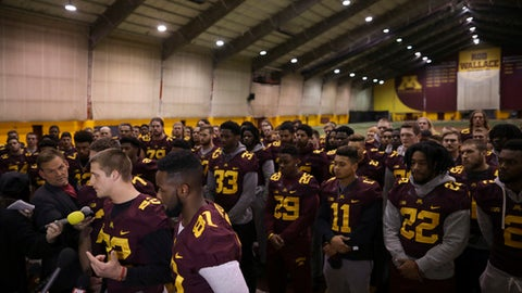 University of Minnesota wide receiver Drew Wolitarsky, flanked by quarterback Mitch Leidner, obscured behind Wolitarsky, and tight end Duke Anyanwu gestures as he stands in front of other team members while talking to reporters in the Nagurski Football Complex in Minneapolis, Minn., Thursday night, Dec. 15, 2016.  The players delivered a defiant rebuke of the university's decision to suspend 10 of their teammates, saying they would not participate in any football activities until the school president and athletic director apologized and revoked the suspensions. If that meant they don't play in the upcoming Holiday Bowl against Washington State, they appeared poised to stand firm. (Jeff Wheeler/Star Tribune via AP)