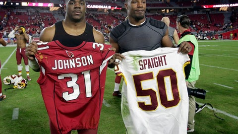 FILE - In this Dec. 4, 2016, file photo, Washington Redskins outside linebacker Martrell Spaight , left, and Arizona Cardinals running back David Johnson swap jerseys after an NFL football game in Glendale, Ariz. Last year Spaight was so sensitive to light that he colored in sunglasses with a black marker. On Dec. 19 night he's set to make his first NFL start for the Washington Redskins under the prime-time lights against Cam Newton and the Carolina Panthers. After losing his entire rookie season to concussion problems, Spaight earned the trust of the coaching staff to fill in for Will Compton at middle linebacker.(AP Photo/Rick Scuteri, File)