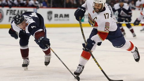 Florida Panthers center Derek MacKenzie, right, takes a shot as Colorado Avalanche defenseman Tyson Barrie defends in the second period of an NHL hockey game Friday, Dec. 16, 2016, in Denver. (AP Photo/David Zalubowski)