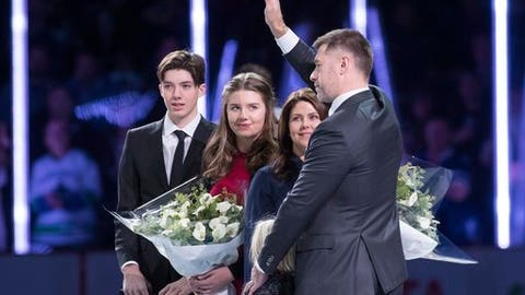 Former Vancouver Canucks' Mattias Ohlund, right, waves to the crowd after being honored by the Canucks organization prior to an NHL hockey game against the Tampa Bay Lightning in Vancouver, British Columbia, Friday, Dec. 16, 2016. (Ben Nelms/The Canadian Press via AP)