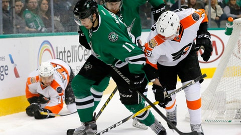 Dallas Stars' Curtis McKenzie (11) and Philadelphia Flyers' Roman Lyubimov (13), of Russia, compete for control of a loose puck during the second period of an NHL hockey game, Saturday, Dec. 17, 2016, in Dallas. (AP Photo/Tony Gutierrez)