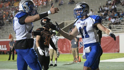 Saint Francis receiver Seth Coate (11) is congratulated by offensive lineman Jaylen Gamble, left, after catching a 5-yard pass for a touchdown during the first half of the NAIA championship football game against Baker in Daytona Beach, Fla., Saturday, Dec. 17, 2016. (AP Photo/Phelan M. Ebenhack)