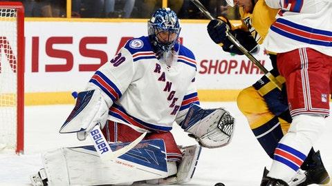 New York Rangers goalie Henrik Lundqvist (30), of Sweden, and Nashville Predators' Craig Smith (15) eye the puck during the second period of an NHL hockey game Saturday, Dec. 17, 2016, in Nashville, Tenn. (AP Photo/Sanford Myers)