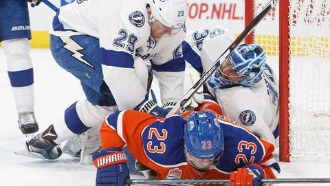Tampa Bay Lightning's Slater Koekkoek (29) and Edmonton Oilers' Matt Hendricks (23) crash into goalie Ben Bishop (30) during the second period of an NHL hockey game in Edmonton, Alberta, Saturday, Dec. 17, 2016. (Jason Franson/The Canadian Press via AP)