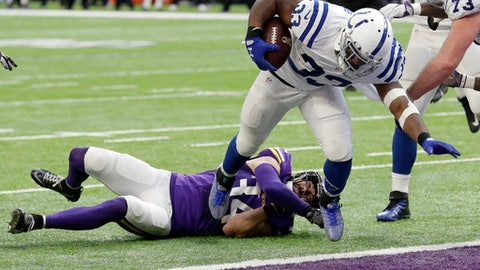 Indianapolis Colts running back Robert Turbin (33) runs past Minnesota Vikings safety Andrew Sendejo on his way to a 6-yard touchdown run during the first half of an NFL football game Sunday, Dec. 18, 2016, in Minneapolis. (AP Photo/Charlie Neibergall)