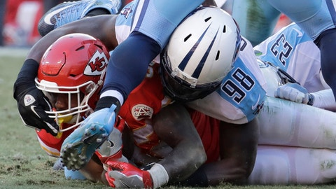 Tennessee Titans linebacker Brian Orakpo (98) grabs the face mask of Kansas City Chiefs running back Spencer Ware (32) during the second half of an NFL football game in Kansas City, Mo., Sunday, Dec. 18, 2016. (AP Photo/Charlie Riedel)