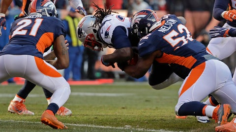 New England Patriots running back LeGarrette Blount scores between Denver Broncos cornerback Aqib Talib, left, and inside linebacker Corey Nelson during the first half of an NFL football game Sunday, Dec. 18, 2016, in Denver. (AP Photo/Jack Dempsey)