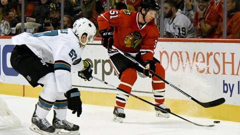 Chicago Blackhawks defenseman Brian Campbell (51) fights for a puck against San Jose Sharks center Tommy Wingels (57) during the first period of an NHL hockey game on Sunday, Dec. 18, 2016, in Chicago. (AP Photo/Matt Marton)