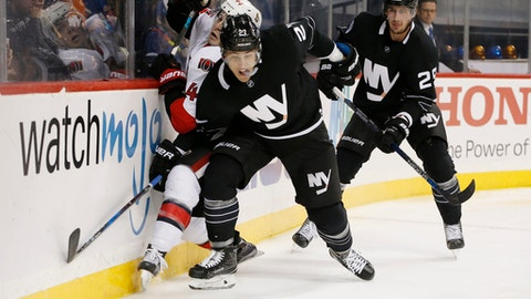 New York Islanders' left wing Anders Lee (27) checks Ottawa Senators' center Jean-Gabriel Pageau (44) during the second period of an NHL hockey game, Sunday, Dec. 18, 2016, in New York. New York Islanders left wing Brock Nelson (29) watches, right. (AP Photo/Kathy Willens)
