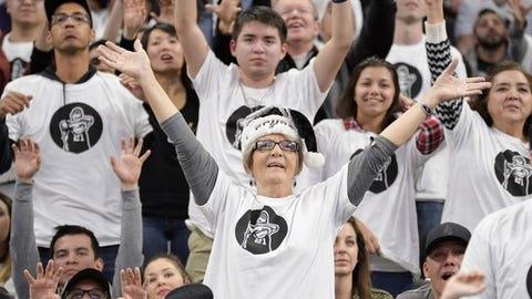 San Antonio Spurs fans wear commemorative Tim Duncan shirts during an NBA basketball game against the New Orleans Pelicans, Sunday, Dec. 18, 2016, in San Antonio. San Antonio won 113-100. (AP Photo/Darren Abate)