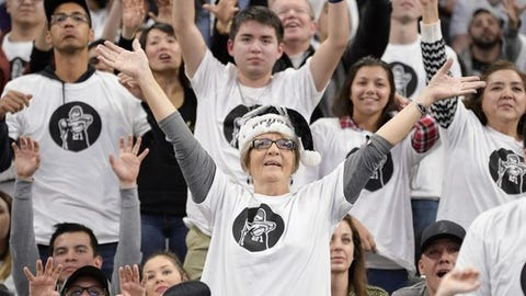 San Antonio Spurs fans wear commemorative Tim Duncan shirts during an NBA basketball game against the New Orleans Pelicans, Sunday, Dec. 18, 2016, in San Antonio. San Antonio won 113-100. (AP Photo/Darren Abate)