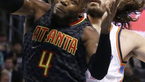 Atlanta Hawks forward Paul Millsap (4) grabs a rebound in front of Oklahoma City Thunder center Steven Adams, right, in the first half of an NBA basketball game in Oklahoma City, Monday, Dec. 19, 2016. (AP Photo/Sue Ogrocki)