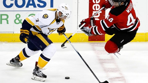 New Jersey Devils left wing Miles Wood, right, goes flying while competing for the puck with Nashville Predators defenseman Yannick Weber, of Switzerland, during the third period of an NHL hockey game, Tuesday, Dec. 20, 2016, in Newark, N.J. The Predators won 5-1. (AP Photo/Julio Cortez)