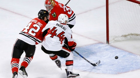 Chicago Blackhawks' Gustav Forsling (42) keeps Ottawa Senators' Jean-Gabriel Pageau (44) from getting a shot on goal as Scott Darling defends during the first period of an NHL hockey game, Tuesday, Dec. 20, 2016, in Chicago. (AP Photo/Charles Rex Arbogast)