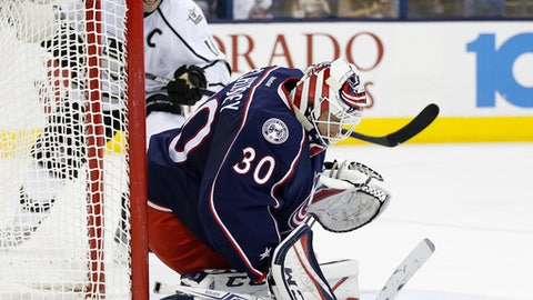 Columbus Blue Jackets' Curtis McElhinney, front, covers the puck after saving a shot against Los Angeles Kings' Anze Kopitar, of Slovenia, during the third period of an NHL hockey game Tuesday, Dec. 20, 2016, in Columbus, Ohio. The Blue Jackets beat the Kings 3-2 in a shootout. (AP Photo/Jay LaPrete)