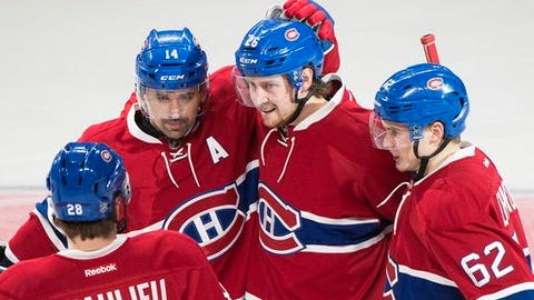 Montreal Canadiens' Jeff Petry (26) celebrates with teammates Tomas Plekanec (14), Nathan Beaulieu (28) and Artturi Lehkonen after scoring against the Anaheim Ducks during the third period of an NHL hockey game, Tuesday, Dec. 20, 2016 in Montreal. (Graham Hughes/The Canadian Press via AP)