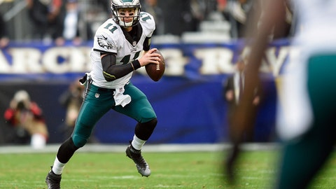 FILE - In this Dec. 18, 2016, file photo, Philadelphia Eagles quarterback Carson Wentz (11) scrambles with the ball during the first half of an NFL football game against the Baltimore Ravens in Baltimore. There's plenty at stake when the Giants (10-4) visit Philadelphia (5-9) on Thursday night.  (AP Photo/Nick Wass, File)
