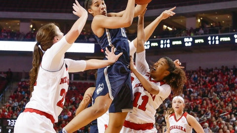 Connecticut's Gabby Williams (15) grabs a rebound between Nebraska's Allie Havers (22) and Esther Ramacieri (11) , with Rylie Cascio Jensen (2) watching, during the first half of an NCAA college basketball game in Lincoln, Neb., Wednesday, Dec. 21, 2016. (AP Photo/Nati Harnik)